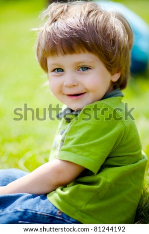 portrait of cute little boy sitting on the grass - stock photo