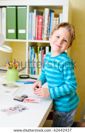 Portrait of cute little boy studying at home
