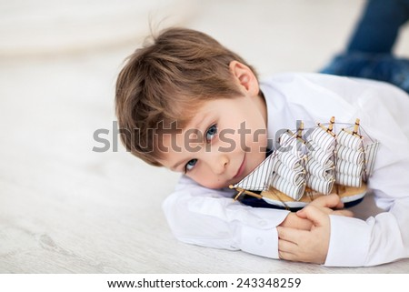 Portrait of cute little boy with ship in his hands - stock photo