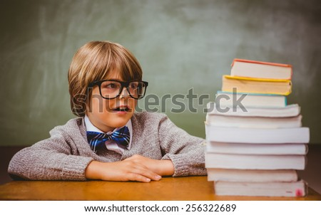 Portrait of cute little boy with stack of books in classroom
