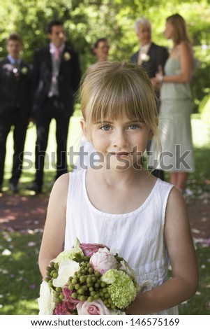 Portrait of cute little bridesmaid holding bouquet in garden with guests and wedding couple in background - stock photo