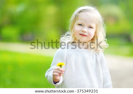 Portrait of cute little cheerful girl outdoors on warm and sunny summer day