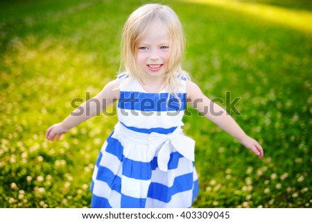 Portrait of cute little cheerful girl outdoors on warm and sunny summer day - stock photo