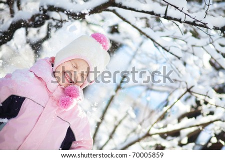 Portrait of cute little child playing with snow outdoors in winter - stock photo