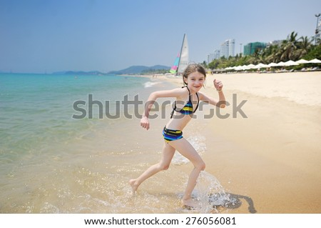 Portrait of cute little girl at tropical beach in the city. Vietnam - stock photo