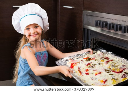 Portrait of cute little girl baking Italian pizza at home