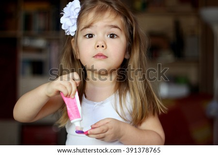 Portrait of cute little girl brushing her teeth, happy family and dental hygiene - stock photo