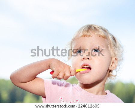 Portrait of cute little girl  brushing teeth  outdoor