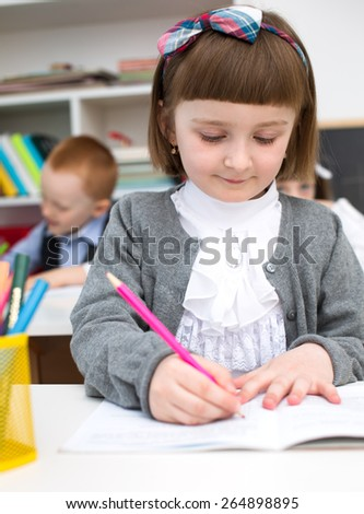 Portrait of cute little girl drawing in copybook