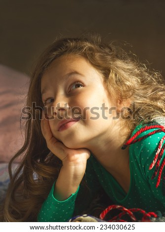 Portrait of cute little girl dreaming in bed