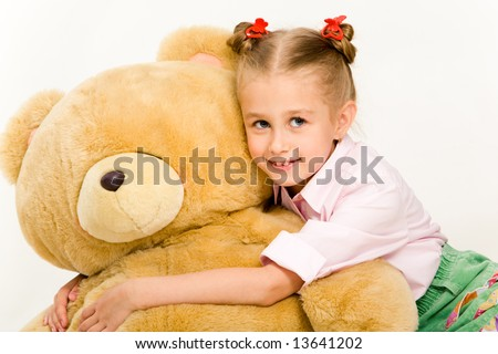 Portrait of cute little girl embracing her teddy bear and smiling - stock photo