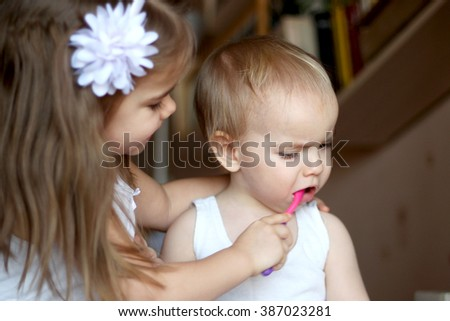 Portrait of cute little girl helping to brush the teeth to her little brother, happy family and dental hygiene - stock photo