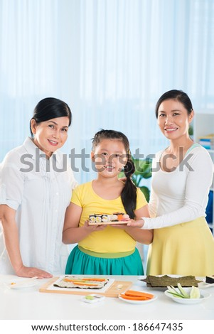 Portrait of cute little girl, her mother and grandmother with homemade sushi looking at camera - stock photo