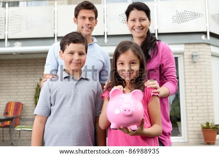 Portrait of cute little girl holding a piggy bank with her family - stock photo