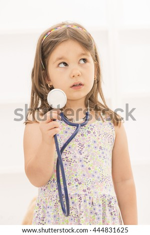 Portrait of cute little girl holding in her hand stethoscope playing doctor looking aside, indoor shot on white room.  - stock photo