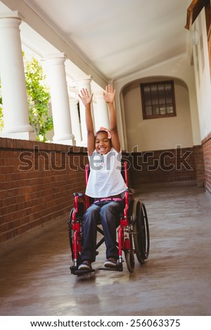 Portrait of cute little girl in wheelchair in school corridor - stock photo