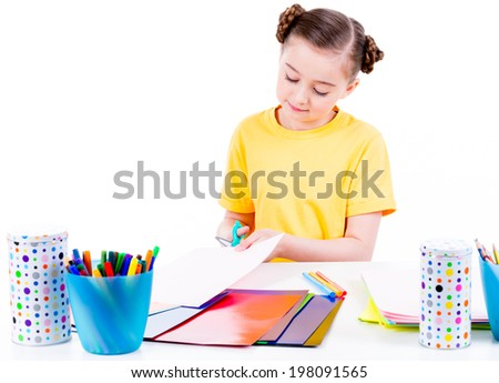 Portrait of cute little girl in yellow t-shirt cut scissor cardboard - isolated on white.