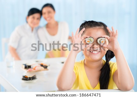 Portrait of cute little girl keeping sushi by her eyes in the kitchen with her mother and grandmother on background - stock photo