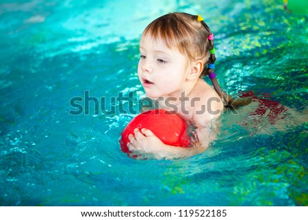 Portrait of cute little girl learning to swim - stock photo