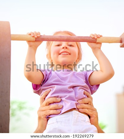 Portrait of cute little girl lifting on horizontal bar outdoors, sportive activities in daycare, summer camp, healthy lifestyle concept