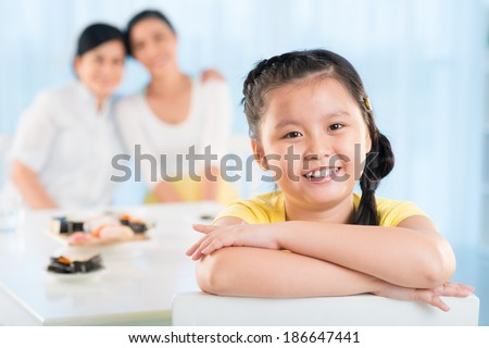 Portrait of cute little girl looking at camera with smile with her mother and grandmother on background - stock photo