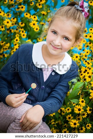 portrait of cute little girl on a background of yellow flowers - stock photo