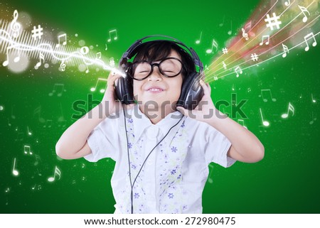 Portrait of cute little girl using headphones to listen the music melody - stock photo