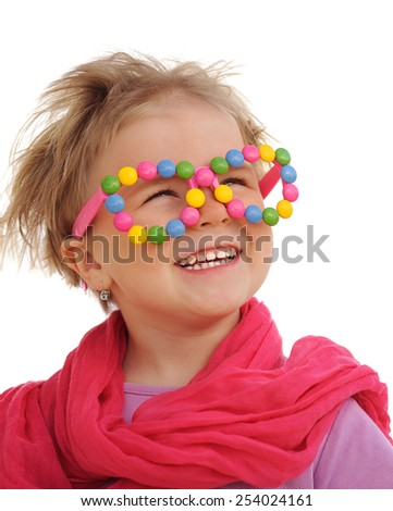 Portrait of cute little girl wearing funny glasses, decorated with colorful candies. Four years old child smiling, having fun. - stock photo