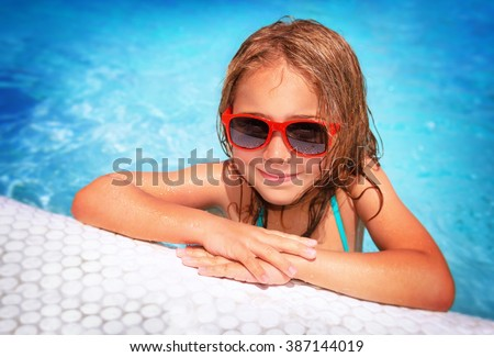 Portrait of cute little girl wearing sunglasses having fun in swimming pool, spending summer vacation on the beach resort - stock photo