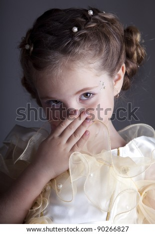 Portrait of cute little girl who hide her mouth.