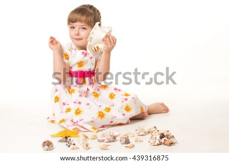 Portrait of cute little girl with a big seashell listening sounds of the sea on white background