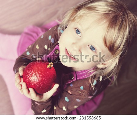 Portrait of cute little girl with a red Christmas bauble. At Christmas time. - stock photo