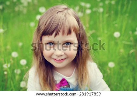 portrait of cute little girl with beautiful smile and blue eyes sitting on the flower meadow, happy childhood concept, child having fun, toned image - stock photo