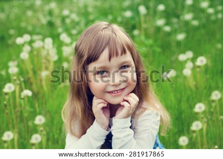 portrait of cute little girl with beautiful smile and blue eyes sitting on the flower meadow, happy childhood concept, child having fun, vintage toned - stock photo