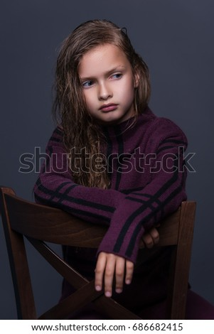 Portrait of cute little girl with dark hair in studio over grey background