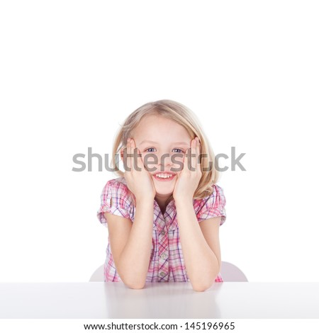 Portrait of cute little girl with hands on cheeks sitting at table isolated over plain background - stock photo