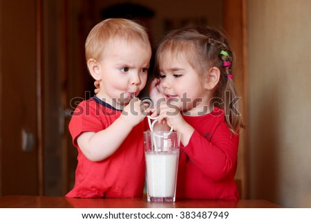 Portrait of cute little girl with handsome toddler boy drinking milk cocktail in a kitchen at home, food and drink concept, healthy food, indoor - stock photo