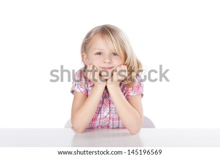 Portrait of cute little girl with head in hands sitting at table isolated over plain background