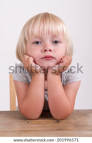 Portrait of cute little girl with head in hands sitting at table isolated over plain background - stock photo