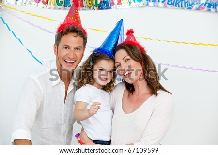 Portrait of cute little girl with her parents during a birthday party at home