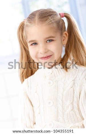 Portrait of cute little girl with ponytail, smiling, looking at camera. - stock photo
