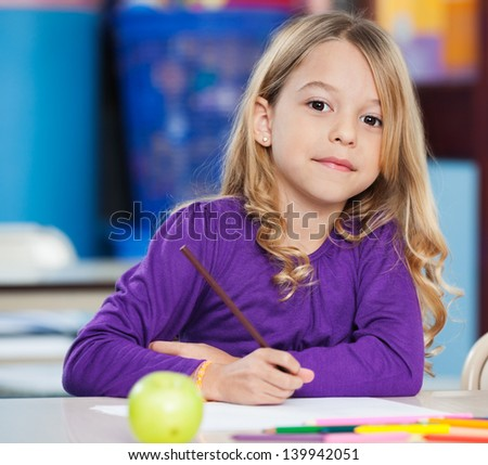 Portrait of cute little girl with sketch pen and paper at desk in class - stock photo