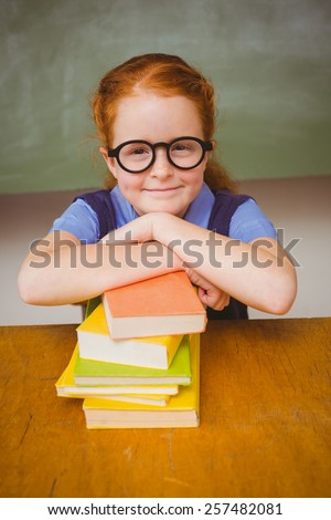 Portrait of cute little girl with stack of books in the classroom - stock photo