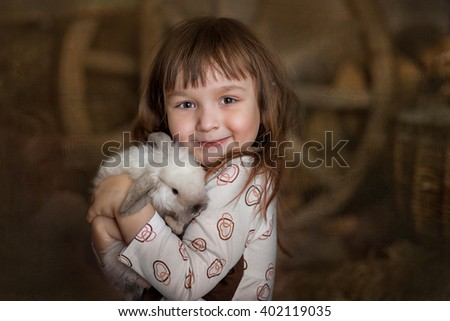 Portrait of cute little girl with white rabbit in hay stack - stock photo