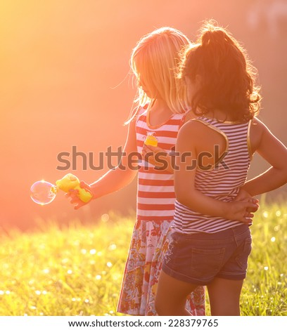 Portrait of cute little girls having bubble fun outdoors - stock photo