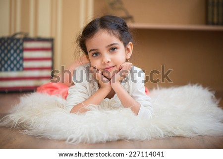 Portrait of cute little latino girl lying on white carpet - stock photo