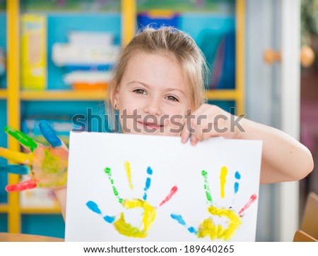 Portrait of cute little preschooler girl with colorful hands - stock photo