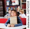 Portrait of cute little schoolboy resting chin on stack of books at table in library with classmates in background - stock photo
