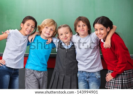 Portrait of cute little schoolchildren with arms around standing together against chalkboard in classroom - stock photo