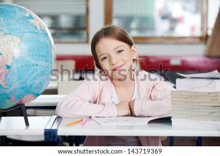 Portrait of cute little schoolgirl smiling with globe and books at desk in classroom